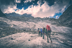 Group of hikers climb the glacier. Instagram stylisation Stock Photo