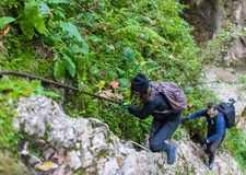 Hikers climbing on mountain wall Stock Images