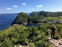 A group of hikers explore the rugged coasts of Newfoundland outside of St. John`s. East Coast Trail, Newfoundland and Labrador, Canada - July 24th, 2017: A group royalty free stock photo
