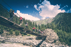 Group of hikers goes above the mountain river. Instagram stylisa Stock Photo
