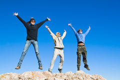 Group of hikers jumping on mountain summit. Three hikers jumping cheerfully on mountain summit in clear sunny weather Royalty Free Stock Photo