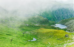 Group of hikers passing through a foggy valley in the Carpathian Royalty Free Stock Photo