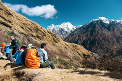 Group of Hikers resting on Trail observing Mountain Panorama Stock Photo
