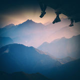 Group of hikers sit above the mountain. Instagram stylisation. Group of hikers sit on a wooden flooring above the mountain valley and enjoy majestic sunset Royalty Free Stock Photography