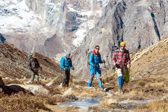 Group of Hikers walking along frozen Creek in Mountain Valley royalty free stock photo