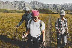 Group Of Hikers Walking Along The Plain In Summer Mountains, Journey Travel Trek Concept. Group Of Hikers Man And Womans With Trekking Poles Walking Along The Royalty Free Stock Photography