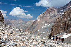 Group of Hikers Walking on Deserted Rocky Terrain Royalty Free Stock Photos