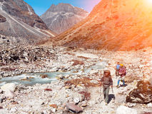 Group of Hikers walking in Mountains along wild Mountain River stock images