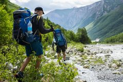 Group of hikers walking in mountains. Tourists with hiking backpacks on beautiful mountain landscape background. Climbers hike royalty free stock photo