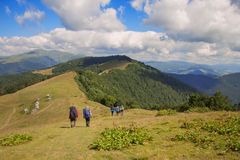 Group of hikers walking on trail. Men and women go with backpack. Group of people walking on trail. Mountain landscape background with blue sky and clouds. Large royalty free stock photos