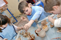 Group of hildren shaping clay in pottery studio Stock Photos