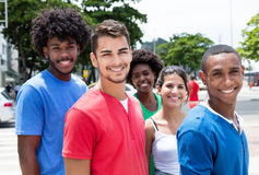 Group of hip young adults with walking in city. With buildings and green plants and trees in the background Stock Photo