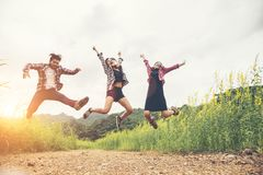 Group of Hipster Teenagers Jumping at the flower field. stock photos