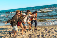 Group of hipster young friends running along beach together. Sea is on background Royalty Free Stock Images