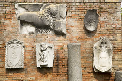 Group of historical ancient sculptures on the brick wall in Torcello island Stock Photo