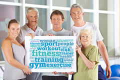 Group holding fitness tag cloud in gym. Senior people group holding fitness tag cloud in gym on cardboard sign Stock Image
