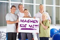 Group holding sign saying German slogan Machen sie mit Stock Photos