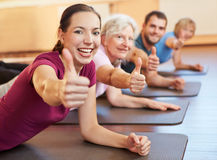 Group holding thumbs up in gym Royalty Free Stock Photography