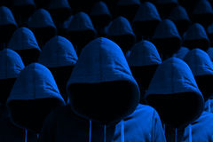 Group of hooded hackers in blue cybersecurity concept Royalty Free Stock Photos