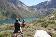 Group of Horseback Riders. A group of horseback riders, riding down a trail torwards a beautiful lake in the mountains Stock Photos