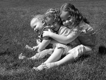 Group hug. Three children on the grass hugging each other close Royalty Free Stock Images