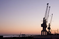 Group of huge sky cranes at a construction site. At sunset, silhouette against orange sky Stock Photo