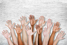 Group of Human Arms Raised with Brick Wall Stock Photography