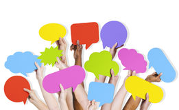 Group of Human Arms Raised with Speech Bubble. Group of human arms raised with multi colored speech bubble Stock Photo