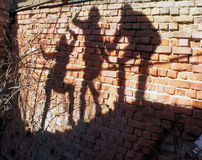 Group of human Shadows on the brick wall Royalty Free Stock Images