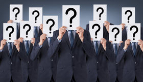 Group of humans hide their faces with question mark. Working Conceptual Business Concept Royalty Free Stock Photo