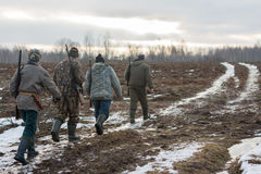 Group of hunters walking on the field Stock Photos