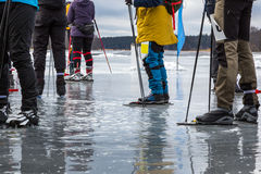 Group of ice skaters on wet melting ice on frozen lake taking a break. Late winter daytime in Sweden. Royalty Free Stock Images