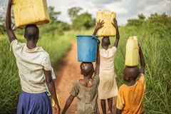 Group if young African kids walking with buckets and jerrycans on their head as they prepare to bring clean water back to their vi. Llage. Part of a non-profit stock image