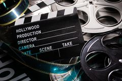 Movie clapper and film reel on a wooden background. A group including a movie clapper and film reels on a wooden background royalty free stock image