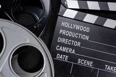 Movie clapper and film reel on a wooden background. A group including a movie clapper and film reels on a wooden background stock images