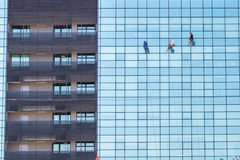 A group of industrial alpinists cleanig windows on a modern skyscraper building stock images
