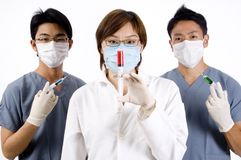 Group Injections. A young medical team holding syringes of different colours Royalty Free Stock Photography