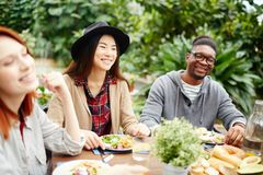 Laughing by dinner. Group of intercultural friends laughing during festive dinner on summer day in the garden Royalty Free Stock Photos