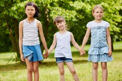 Group of girls at the park. Group of intercultural girls at the park holding hands together as friends Royalty Free Stock Images