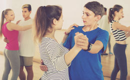 Group of interested teenagers dancing tango in dance studio Stock Images