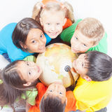 Group of international kids holding globe earth Royalty Free Stock Images