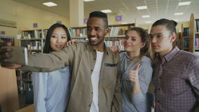 Group of international students have fun smiling and making selfie photos on smartphone camera at university library. Indoors. Cheerful friends have rest while stock video footage
