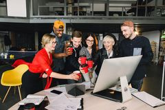 Group of international students or workers in loft office clinking cups of coffee, six colleagues of modern work co stock photo