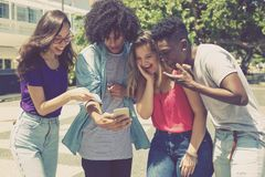 Group of international young adults gaming with phone stock image