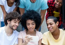 Group of international young adults looking at phone royalty free stock photography