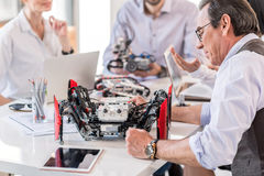Group of inventors constructing devices in office Stock Photo