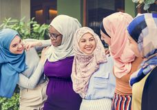 Group of islamic friends arms around and smiling together stock images