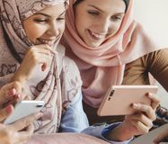 Group of islamic women talking and watching on the phone together stock photos