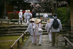 Group of Japanese pilgrims. Kochi, Japan - March 29, 2009: A group of Japanese pilgrims enters the territory of Shingon temple in the Kochi city on Shikoku Stock Photo