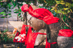 Group of jizo statues. Statues of Jizo, the protector of travellers and children, dressed in red hats and bibs.  Red represents safety and protection Royalty Free Stock Image